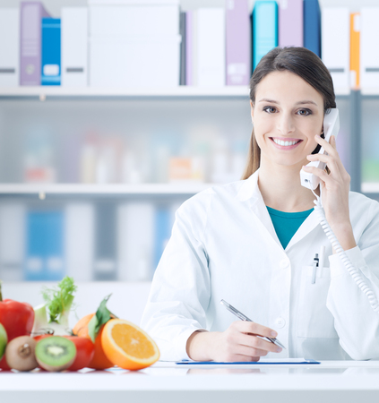 Smiling nutritionist having a phone call and scheduling appointments, healthy eating and healthcare concept Zdjęcie Seryjne