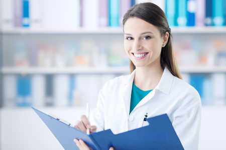 Smiling female doctor in the office holding a clipboard with medical records and writing