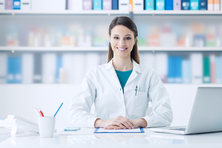 Young smiling female doctor sitting at office desk and looking at camera, healthcare concept