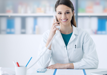 Smiling female doctor working at office desk and answering phone calls, healthcare and consulting concept Reklamní fotografie