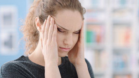 Young woman touching her temples and having a bad headache, stress and exhaustion concept