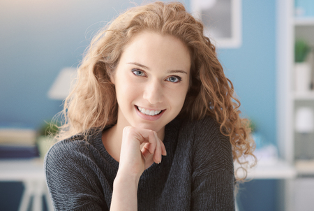 Beautiful curly young woman posing at home with hand on chin, she is smiling at camera Imagens