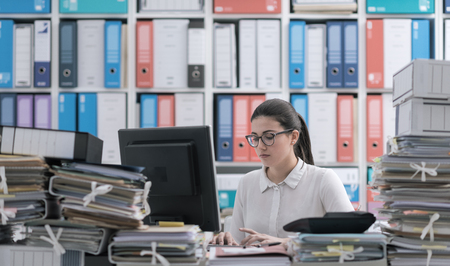 Young confident businesswoman working at office desk and typing, piles of paperwork on the foreground