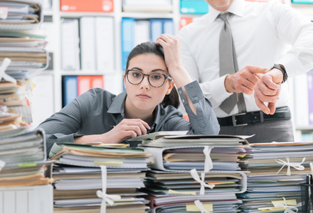 Demanding boss pointing to his watch and asking to his employee to hurry up, his secretary is frustrated and overwhelmed by work: business and deadlines concept Stok Fotoğraf