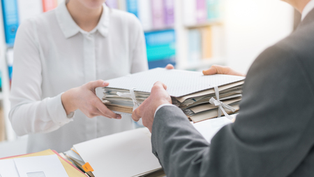 Boss handing paperwork to his young female employee