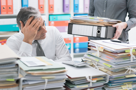 オフィスデスクで働き、仕事で過負荷のビジネスマンを強調し、デスクトップは書類で覆われており、彼の秘書はより多くのファイルをもたらしています 写真素材 - 101210305