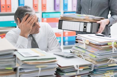 Gestresster Geschäftsmann, der am Schreibtisch arbeitet und mit Arbeit überlastet ist, der Desktop ist mit Papierkram bedeckt, seine Sekretärin bringt mehr Akten