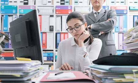 Boss watching over his young employee and standing behind her, she is working and feeling oppressed