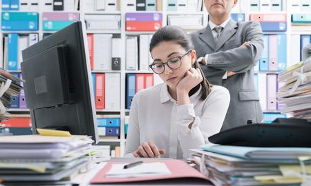 Patron veillant sur son jeune employé et debout derrière elle, elle travaille et se sent opprimée Banque d'images