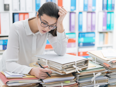 Frustrated you office worker leaning on piles of paperwork, she is overloaded with work and stressed Фото со стока