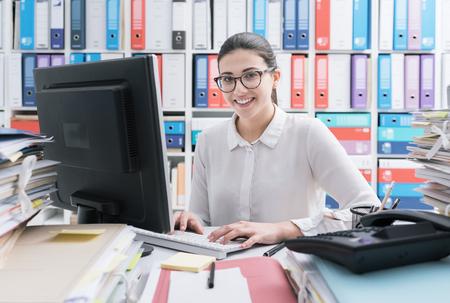 Młoda uśmiechnięta sekretarka pracuje przy biurku i wpisując na klawiaturze