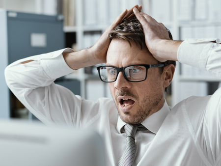 Panicking businessman with head in hands in his office, he is receiving shocking bad news on his computer 版權商用圖片