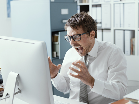 Angry business executive shouting at the computer, stressful job and system failure concept 스톡 콘텐츠