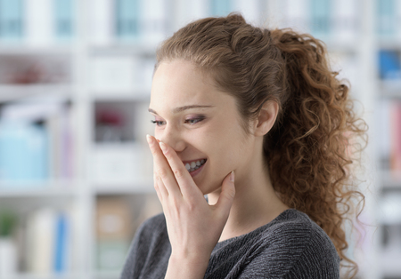 Cute young teenage girl giggling and covering her mouth with her hand