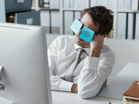 Luie, onproductieve kantoormedewerker die grappige plaknotities op zijn bril draagt en zijn gesloten ogen verbergt Stockfoto