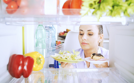 Undecided woman holding healthy vegetables and a dessert, she is choosing what to eat and comparing food, healthy lifestyle and diet concept Stock Photo