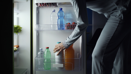 Woman taking a bottle of milk from the fridge late at night, lifestyle and diet concept