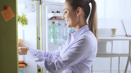 Young smiling woman taking food from the fridge and preparing lunch, healthy lifestyle and food preparation concept
