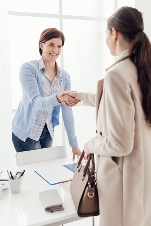 Business meeting in the office, a businesswoman is giving an handshake to the customer; job interview and agreement concept Stock Photo