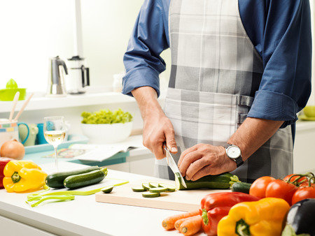 Man preparing lunch in the kitchen, he is slicing fresh healthy vegetables on the chopping board, healthy food concept Stock Photo