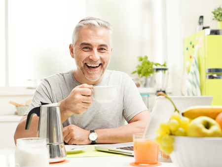 Smiling mature man having an healthy breakfast at home, he is sitting at the kitchen table, drinking coffee and connecting with his laptop Reklamní fotografie - 103482559