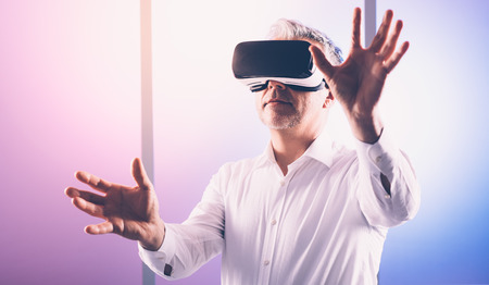 Mature man wearing a VR headset and interacting with a virtual reality environment Banco de Imagens