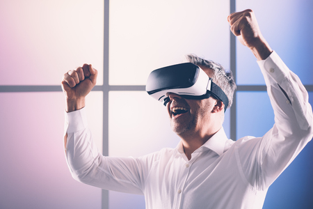 Cheerful man enjoying virtual reality, he is smiling with raised fists and wearing a VR headset