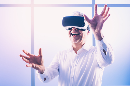 Mature man wearing a VR headset and interacting with a virtual reality environment 스톡 콘텐츠