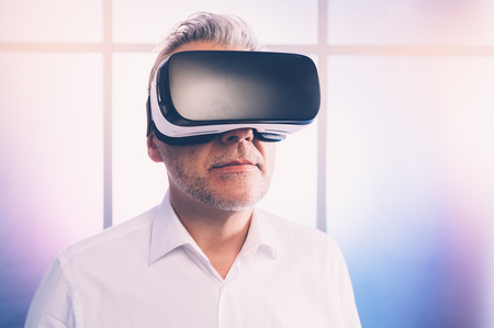 Mature man experiencing virtual reality, he is wearing a VR headset, technology and innovation concept 스톡 콘텐츠