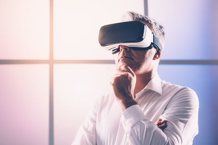 Mature man experiencing virtual reality, he is wearing a VR headset, technology and innovation concept Stock Photo