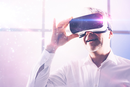 Smiling man interacting with a virtual reality environment, he is wearing a VR headset