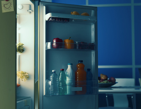Open fridge in the kitchen with healthy fresh food and drinks Stock Photo