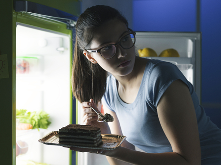 Woman in the kitchen having a late night snack, she is taking a delicious dessert from the fridge, diet fail concept Фото со стока