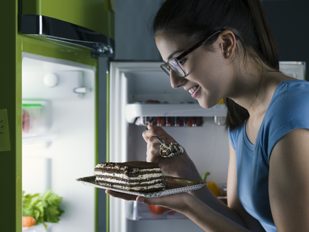 Woman in the kitchen having a late night snack, she is taking a delicious dessert from the fridge, diet fail concept 写真素材