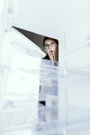 Young hungry desperate woman looking into her empty fridge, she is panicking