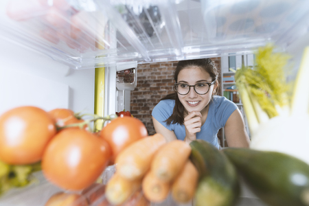 Young smiling woman preparing an healthy fresh meal, fridge interior and groceries on the shelves Stock Photo