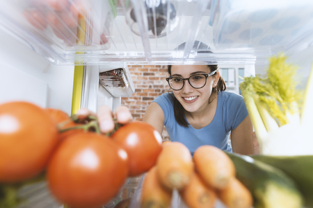 Young smiling woman preparing an healthy fresh meal and taking vegetables, fridge interior and groceries on the shelves Standard-Bild