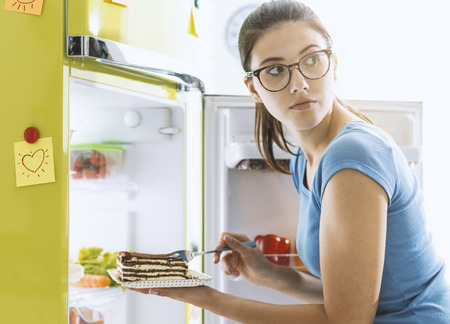 Hungry young woman taking a delicious dessert from the fridge and having a snack, diet fail concept