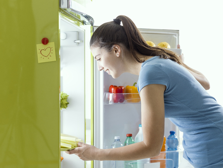 Smiling woman taking some fresh celery from the fridge and preparing an healthy meal at home