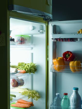 Open fridge in the kitchen with healthy fresh food and drinks Stock fotó