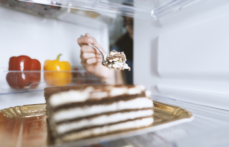 Hungry woman eating a dessert straight from the fridge using a fork, diet fail concept Фото со стока