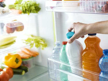 Femme prenant une bouteille de lait frais du concept de réfrigérateur, de nutrition et de régime