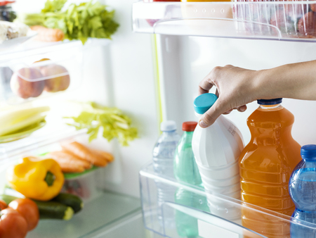 Woman taking a bottle of fresh milk from the fridge, nutrition and diet concept