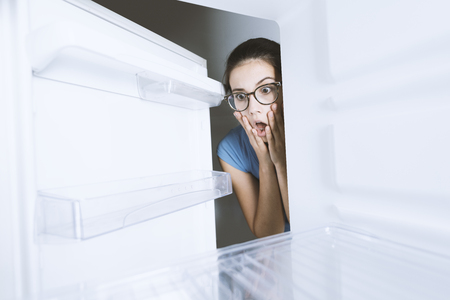 Young hungry desperate woman looking into her empty fridge, she is panicking Foto de archivo - 103534734