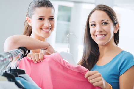 Teenagers shopping womens clothing at the store and smiling at camera, customer satisfaction and quality concept 写真素材