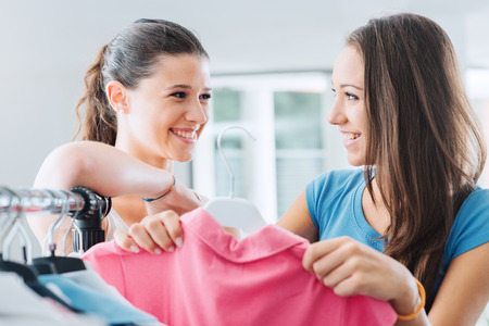 Happy smiling teenager girls shopping at the store and having fun, one is holding a pink shirt