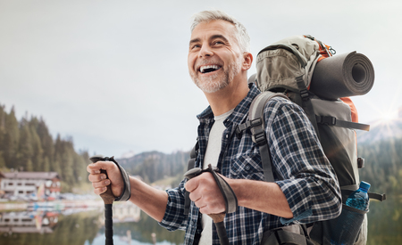 Confident mature man doing nordic walking on the mountains, he is using trekking poles and carrying a backpack, freedom and sports concept