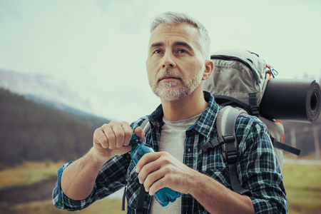 Confident mature hiker trekking on the mountains and opening a water bottle, fitness and sports concept Stock Photo - 114191218