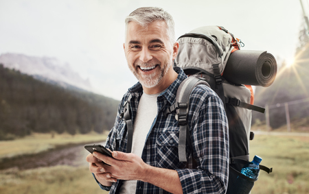 Hiker walking on the mountains and exploring nature, he is connecting with a smartphone and using apps Stock Photo