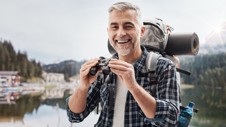 Smiling mature hiker exploring mountains and holding binoculars, travel and wilderness concept Stock Photo - 114191221
